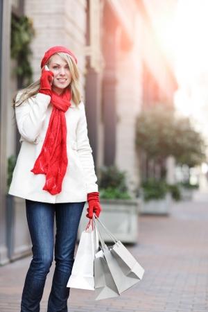 Een Kaukasische vrouw boekwaarde boodschappentassen winkelen en praten over de telefoon op een outdoor shopping mall Stockfoto