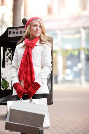 A shopping caucasian woman carrying shopping bags at an outdoor shopping mall photo