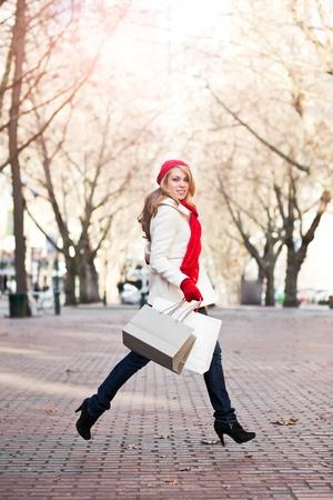 A shopping caucasian woman carrying shopping bags at an outdoor shopping mall