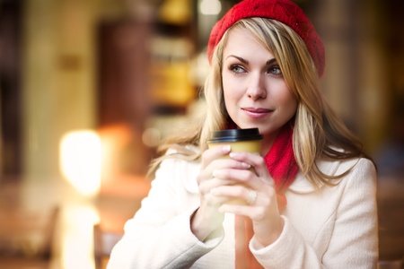 A shot of a beautiful caucasian woman drinking coffee at a cafe photo