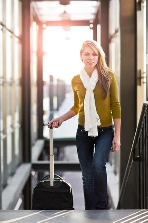 persona viajando: Un tiro de una hermosa joven caucásica tirando un equipaje de viaje
