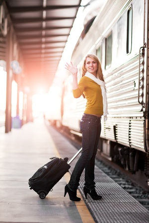 A shot of a beautiful young Caucasian woman traveling pulling a luggage photo
