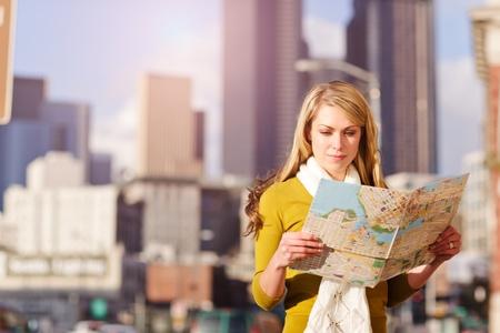 A shot of a beautiful caucasian traveling woman reading a map