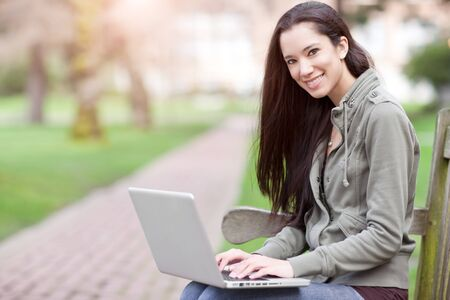 native american ethnicity: A shot of a beautiful ethnic college student working on her laptop on campus