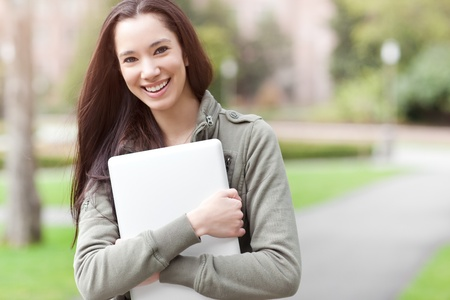 A shot of an ethnic college student carrying a laptop on campus photo