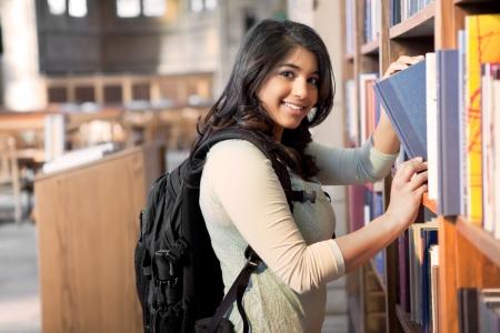 Un disparo de un estudiante asiático obtener libros en una biblioteca Foto de archivo - 9197801