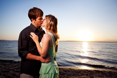 love kissing: A romantic caucasian couple in love kissing on the beach