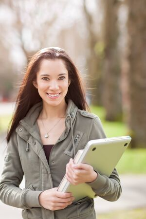 A shot of an ethnic college student carrying a book and a laptop on campus Stock Photo - 9249162