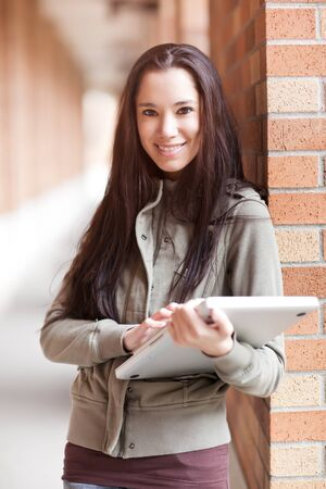 A shot of an ethnic college student carrying a laptop on campus Stock Photo - 9249156