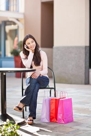 彼女の電話で話しているショッピング アジア女性