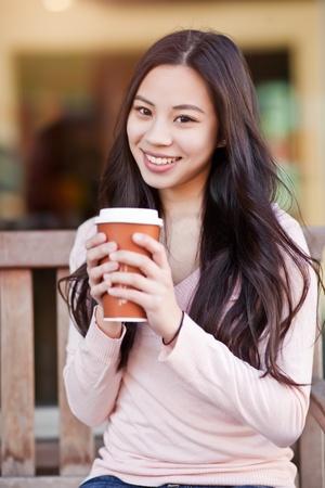 Een schot van een mooie Aziatische vrouw drinken koffie buiten