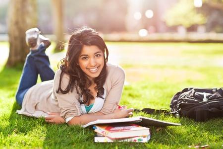 キャンパスの芝生の上を勉強して、アジア留学生のショット