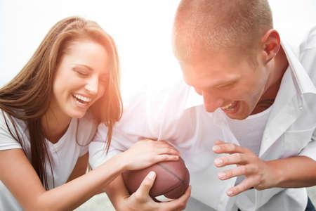 jugando futbol: Una hermosa feliz pareja cauc�sica divertirse jugando f�tbol
