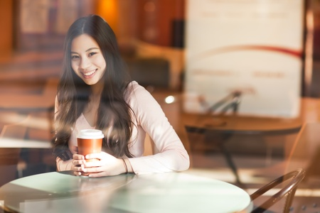 A shot of a beautiful asian woman drinking coffee in a cafe photo