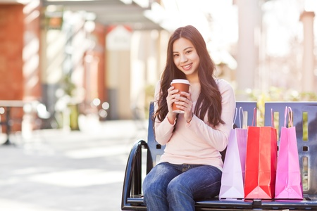 A shot of a beautiful shopping asian woman drinking coffee outdoor 版權商用圖片