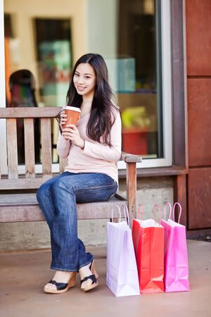 Een schot van een mooie winkelstraat Aziatische vrouw drinken koffie buiten