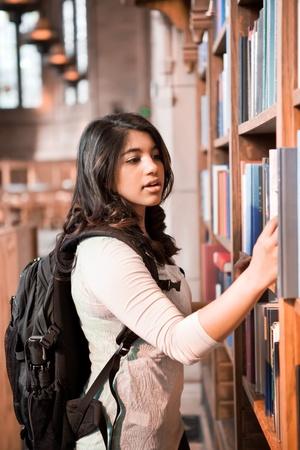 ライブラリに書籍を取得する、アジアの留学生のショット