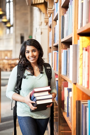 A shot of an asian student holding books at the library photo