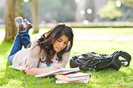 study: A shot of an asian student studying on campus lawn