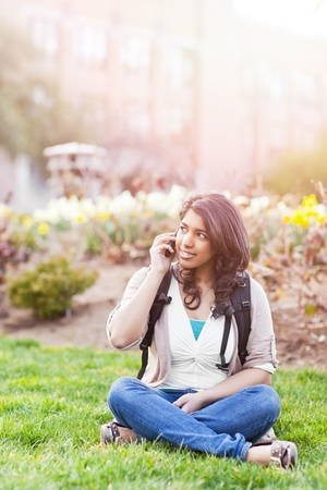woman on phone: A shot of an asian student talking on the phone on campus