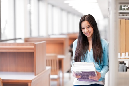 A portrait of an Asian college student holding books in the library photo
