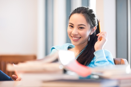 A portrait of an Asian college student studying in the library Stock Photo - 9518966