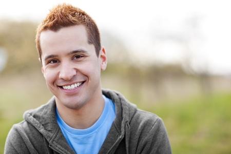 headshot: A shot of a mixed race man smiling outside