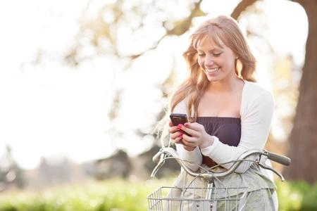 야외에서 그녀의 전화에 아름다운 젊은 백인 여자 문자 메시지의 초상