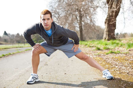 A shot of a mixed race man stretching outdoor Banco de Imagens