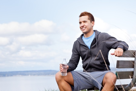 water activity: A shot of a mixed race man holding water bottle outdoor