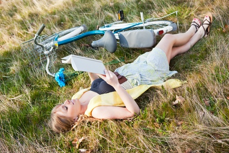lying down: A portrait of a beautiful young Caucasian woman reading a book outdoor
