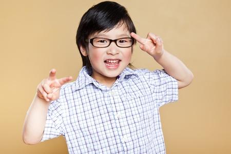 재미 있은 얼굴을 만드는 귀여운 아시아 소년의 초상화