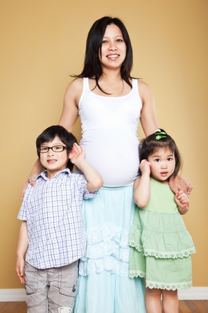 A shot of a pregnant Asian mother with her two kids Фото со стока