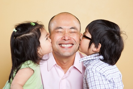 A shot of an Asian father kissed by his kids Фото со стока
