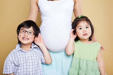A shot of a pregnant Asian mother with her two kids photo
