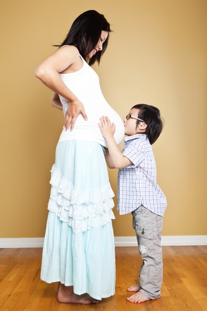 kissing pregnant belly: A shot of an Asian boy kissing the belly of his pregnant mother