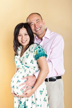 그녀의 남편과 아름 다운 임신 아시아 여자의 총