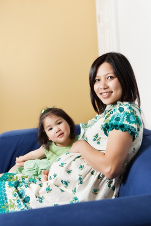 A shot of a pregnant Asian woman sitting on the couch with her daughter photo