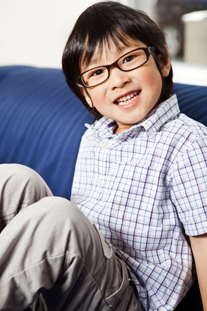 A portrait of a cute asian boy sitting on a sofa at home photo