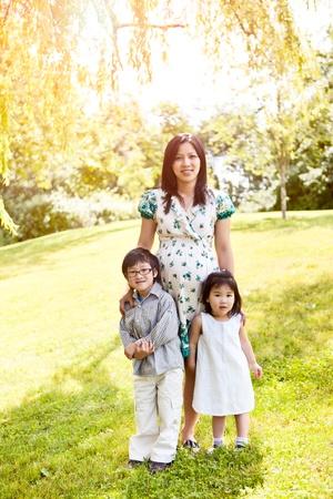 그녀의 두 아이가 야외와 함께 임신 아시아 어머니의 총 스톡 콘텐츠 - 10264735