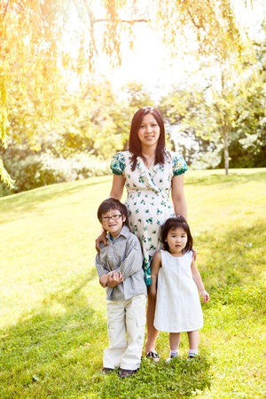 A shot of a pregnant Asian mother with her two kids outdoor photo