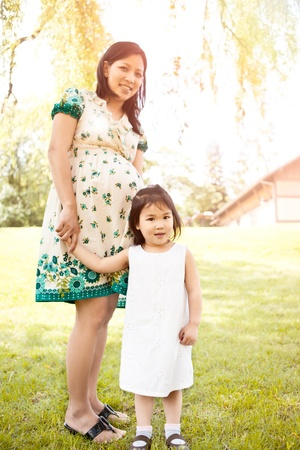 A shot of a little Asian girl and her pregnant mother photo