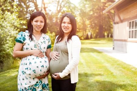 A shot of two beautiful pregnant Asian women photo
