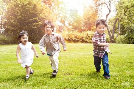 niños jugando en el parque: Un tiro de tres niños asiáticos que se ejecutan en un parque (foco en el medio kid) Foto de archivo