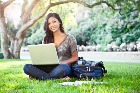 asian laptop: A shot of an Asian student working on laptop on campus