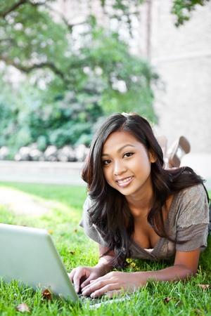 캠퍼스에서 노트북에 근무하는 아시아 학생의 샷