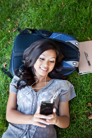 A shot of an Asian college student listening to music lying down on the grass on campus