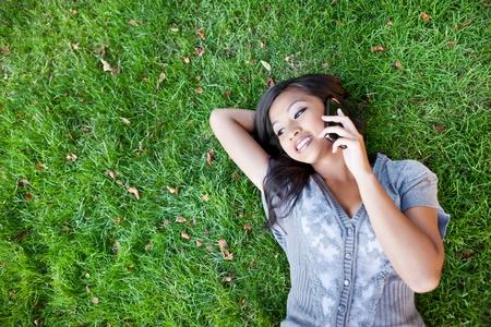 amigas conversando: Un disparo de un estudiante asi�tico hablando por tel�fono