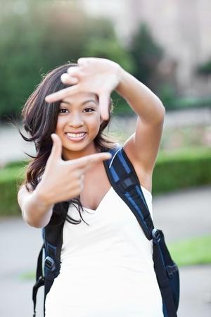 그녀의 손으로 프레임 만들기 아시아 학생의 샷