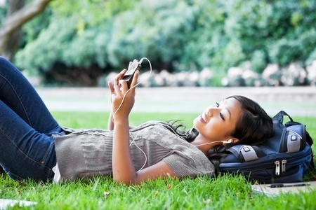 A shot of an Asian college student listening to music lying down on the grass on campus photo